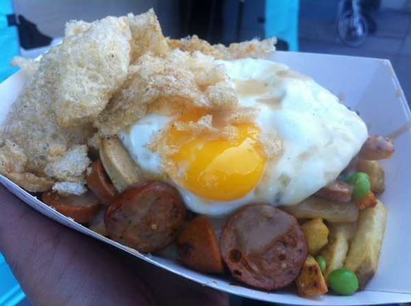 Sausage and crispy fries with gravy, English peas, sunny side up egg and chicharrones- it&#039;s for lunch. 
